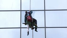Sanitation worker cleaning glass facade hotel stock footage