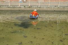 Sanitation workers clean up the rubbish in the river Royalty Free Stock Photo