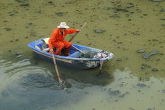 Sanitation workers clean up the rubbish in the river Royalty Free Stock Images