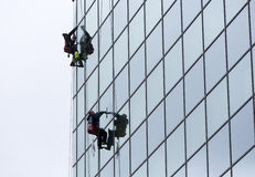 Sanitation workers cleaning glass facade hotel Stock Images