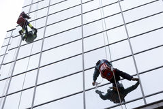 Sanitation workers cleaning glass facade hotel Stock Photos