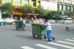The sanitation workers push the rubbish bin through the road Royalty Free Stock Photography
