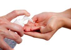Sanitizer de doação adulto da mão da criança Imagens de Stock Royalty Free