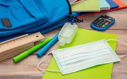 Sanitizer gel, medical mask and school supplies on a student desk