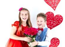 Sankt dag för valentin` s Den nätta flickan med den röda klänning- och gentlemanpojken med den blåa västen, rött fjärilsband, röd arkivfoto