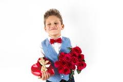 Sankt dag för valentin` s Den stiliga gentlemanpojken med den blåa västen, rött band, röda rosor ösregnar och röda ballonger Vale royaltyfria foton