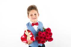Sankt dag för valentin` s Den stiliga gentlemanpojken med den blåa västen, rött band, röda rosor ösregnar och röda ballonger Vale arkivfoto