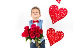 Sankt dag för valentin` s Den stiliga gentlemanpojken med den blåa västen, rött band, röda rosor ösregnar och röda ballonger Vale fotografering för bildbyråer