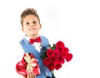 Sankt dag för valentin` s Den stiliga gentlemanpojken med den blåa västen, rött band, röda rosor ösregnar och röda ballonger Vale arkivbild