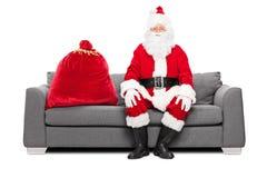 Sankt, die auf einem Sofa mit Geschenkesack sitzt Stockfotografie