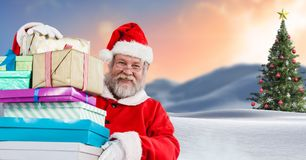 Sankt, die Geschenke in der Weihnachtswinterlandschaft mit Weihnachtsbaum hält Lizenzfreies Stockfoto