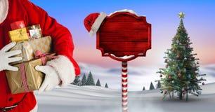 Sankt, die Geschenke halten und hölzerner Wegweiser im Weihnachtswinter gestalten mit Weihnachtsbaum landschaftlich Stockfotografie
