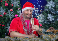 Sankt, die mit Glas Wein auf Weihnachtshintergrund aufwirft Stockfotografie