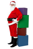 Sankt, die neben Stapel von Weihnachtsgeschenken steht Lizenzfreies Stockbild