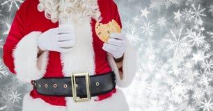 Sankt, die Plätzchen mit Milch und Schneeflocken-Weihnachtsmuster isst Stockfotos