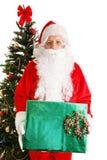 Sankt durch Weihnachtsbaum mit Geschenk stockfotos