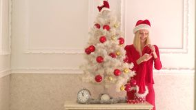 Sankt-Frau, die Weihnachtsgeschenkbox an der weißen Wand hält Sinnliche Frau Modeportr?t des vorbildlichen M?dchens zuhause mit stock video footage