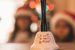 Sankt-Glocke mit Weihnachtslichtern und -kindern im Hintergrund Stockbild