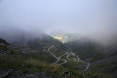 Sankt Gotthard (Pass). View down on serpentines from the Sankt Gotthard (Pass) through mist to light stock photo