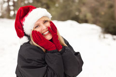 Sankt-Hut, der die blonde Frau hat Spaß im Schnee trägt Stockfoto