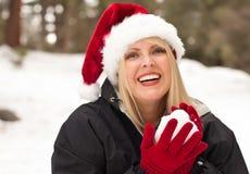 Sankt-Hut, der die hübsche Frau hat Spaß im Schnee trägt Stockfotografie