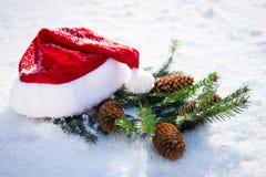 Sankt-Hut mit Tannenzweig auf Schnee Lizenzfreies Stockfoto