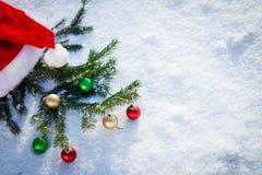Sankt-Hut mit Tannenzweig auf Schnee Lizenzfreie Stockfotos