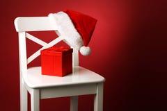 Sankt-Hut und rote Geschenkbox mit rotem Bogen auf weißer Stuhlfront des roten Hintergrundes Lizenzfreies Stockfoto