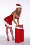 Sankt im roten Kleid mit den entfernten Strümpfen, die über Geschenk-Beutel verbiegen Lizenzfreie Stockfotografie