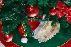 Sankt-Kappe mit Geldbrasilianer Geld für Weihnachtsgeschenke oder Geschenkgeld Weihnachtsniederlassung und -glocken lizenzfreie stockfotos