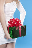 Sankt-Mädchen, das ein Geschenk versteckt Stockbild