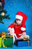 Sankt-Mädchen, das mit Cristmas Geschenken spielt Stockfoto