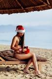 Sankt-Mädchen im Bikini, der Weihnachtsgeschenk auspackt Lizenzfreies Stockfoto