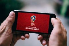 SANKT PETERSBURG, RUSLAND - APRIL 20, 2018: Close-up van het iPhonescherm met WORLDCUP 2018 van FIFA EMBLEEM in Rusland Stock Foto