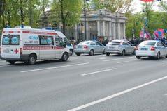 Sankt- Petersburg, Rusland - Mei 28, 2017: De ziekenwagen komt voor politiewagens langs de straat van de stad Sankt- Petersburg,  Royalty-vrije Stock Foto's