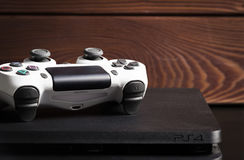 Sony PlayStation 4 Slim 1Tb revision and game controller on the wood surface. Stock Photos