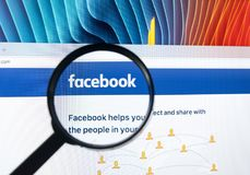 Homepage of Facebook.com on Apple iMac monitor screen under magnifying glass. Royalty Free Stock Photos