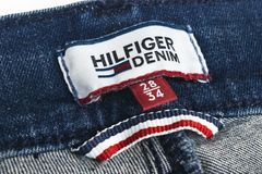 Closeup of Tommy Hilfiger label on blue jeans. Tommy Hilfiger is lifestyle brand. Hilfiger Denim. Tommy Hilfiger blue jeans detai Stock Photos