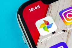Google Photos plus application icon on Apple iPhone X screen close-up. Google plus Photos icon. Google photos application. Social. Sankt-Petersburg, Russia stock image