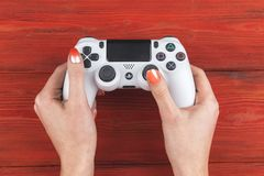 Sony PlayStation 4 dualshock game controller in gamers hand on wood background studio shot.  Game console with a joystick. Sankt-Petersburg, Russia, September Royalty Free Stock Image