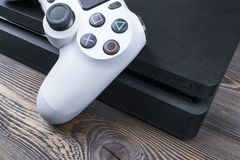 Sony PlayStation 4 Slim 1Tb revision and dualshock game controller. Game console with a joystick. Home video game console on wood. Sankt-Petersburg, Russia royalty free stock photography