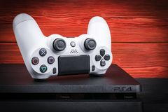 Sankt-Petersburg, Russia, September 24, 2017: Sony PlayStation 4 Slim 1Tb revision and dualshock game controller on the red wood Stock Photo