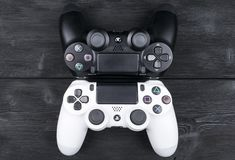 Sony PlayStation 4 Slim 1Tb revision and 2 dualshock game controller on the wooden table background. Home video game console Stock Photos