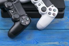 Sony PlayStation 4 Slim 1Tb revision and 2 dualshock game controller on the wooden table background. Home video game console. Sankt-Petersburg, Russia, September stock photography