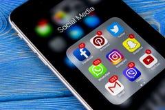 Sankt-Pietroburgo la Russia 11 novembre 2017: IPhone di Apple 7 più sulla tavola di legno blu con le icone del facebook sociale d Immagine Stock