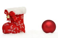 Sankt roter Stiefel mit einem Flitter im Schnee auf Weiß Lizenzfreie Stockbilder