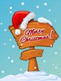 Sankt-` s Hut auf einem hölzernen Zeiger mit Weihnachtsgrüßen Lizenzfreies Stockfoto