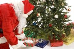 Sankt setzt Geschenke unter Baum stockbild