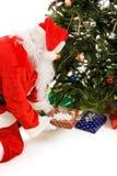Sankt setzt Geschenke unter den Baum Stockfotografie