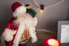 Sankt steht auf einem Regal mit Girlanden und Kerzen Stockbilder
